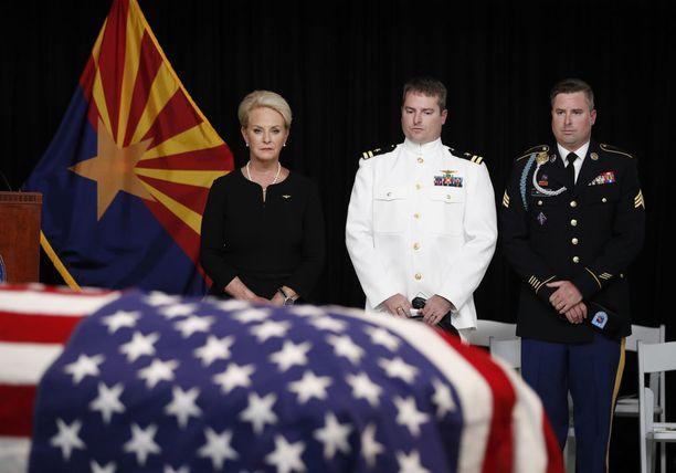 Cindy McCain poikiensa Jackin ja Jimmyn rinnalla muistotilaisuudessa.