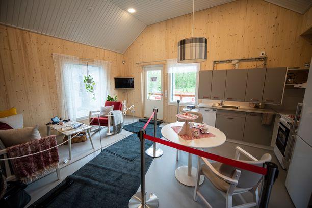 Olohuone ja keittiö ovat samaa tilaa. Messujen takia asuntoa on rajattu ja lattialla on harmaita mattoja.