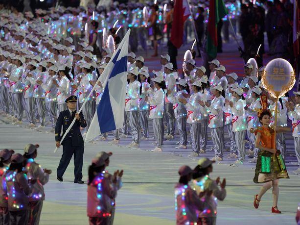 Sotilaiden MM-kisat alkoivat perjantaina näyttävillä avajaisilla. Kuvassa Wuhan Sports Center  Stadiumille kannetaan Suomen sinivalkoista lippua.