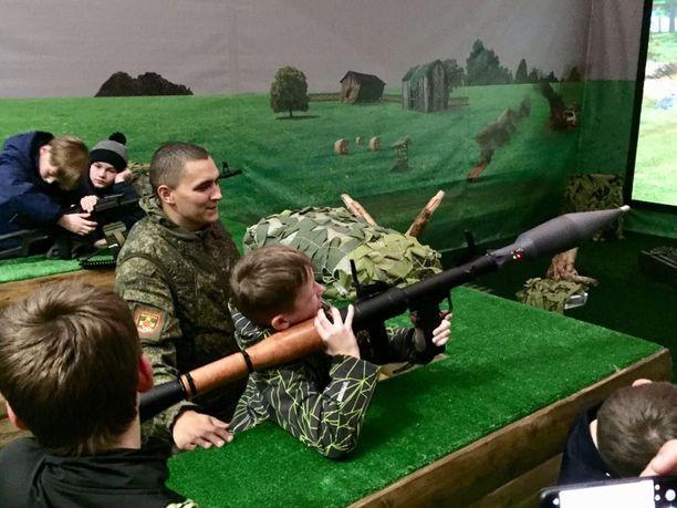 Kouluttaja näyttää lapsille kuinka tankkeja tuhotaan kevytsingolla.