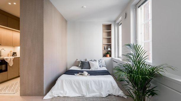 Jykevän seinän takaa paljastuu yksiön valoisa ja tunnelmallinen alkovi. Vaaleat luonnonvärit ja viherkasvit tuovat kodikasta tunnelmaa sekä seinään upotettu kirjahylly on kätevä iltalukemista ajatellen.
