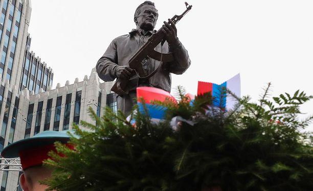 AK-47 -ase on patsaassa näyttävästi esillä.