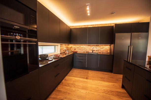 Mustat keittiöt ovat nyt suosittuja. Tässä volyymia keittiöön tuo myös tiiliseinä.