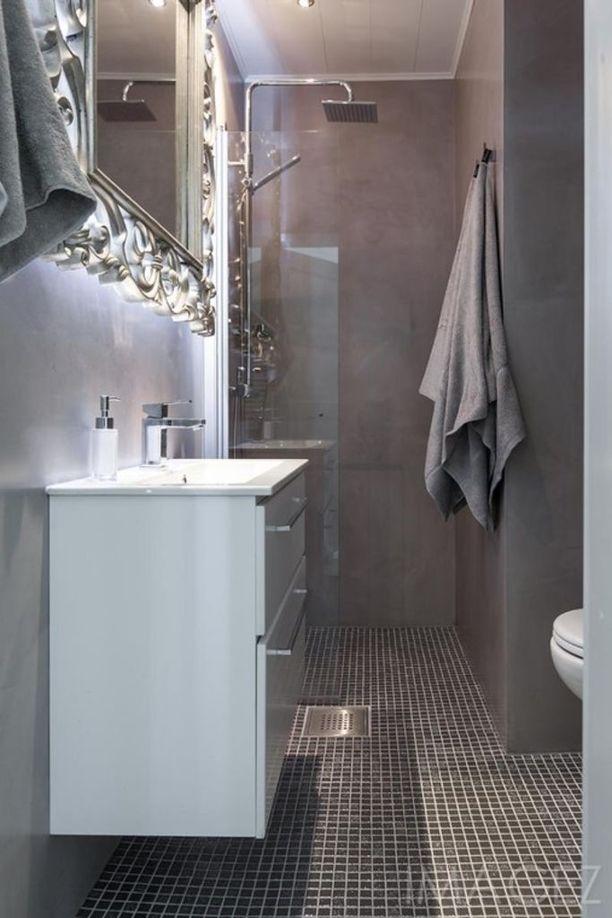 Tässä kylpyhuoneessa betonimaiset mikrosementtiseinät on yhdistetty pieneen tummaan mosaiikkilaattaan. Muu sisustus korostaa huoneen glamouria tunnelmaa.