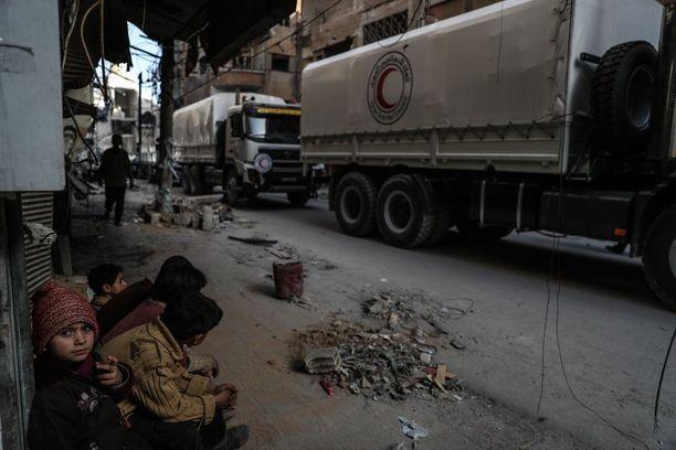 Lapset katselivat, kun Punaisen Puolikuun avustusrekat saapuivat Itä-Ghoutan Doumaan sunnuntaina ensi kertaa viikkoihin.