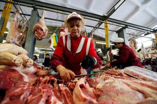 Nainen myi lihaa torilla Moskovassa. Kuva on viime vuoden joulukuulta.