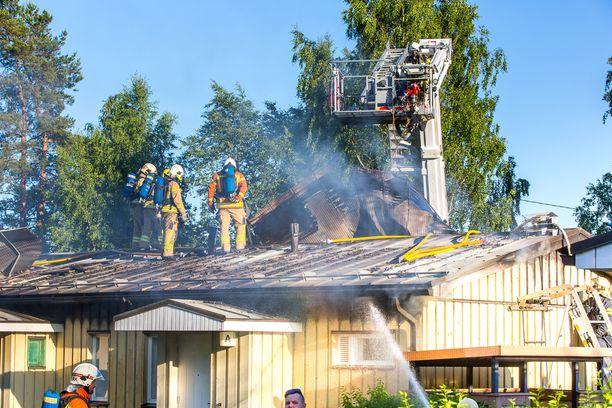 Pelastuslaitos irrotti kattopeltejä päästäkseen käsiksi palopesäkkeisiin.