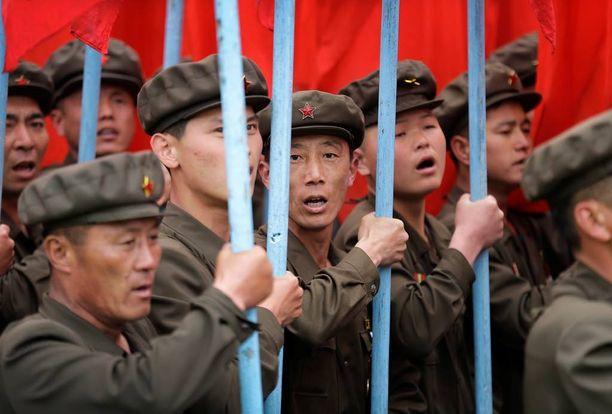 Paraatissa kannettiin puolueen lippuja. Pohjois-Koreassa on yksipuoluejärjestelmä ja valta on periytynyt isältä pojalle 1940-luvulta lähtien.