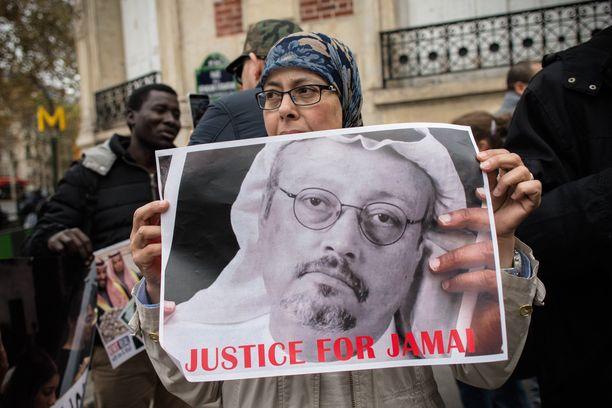 """""""Oikeutta Jamalille"""". Nainen osoittaa mieltään Saudi-Arabian lähetystön edustalla 25. lokakuuta Pariisissa kantaen Khashoggin kuvaa."""
