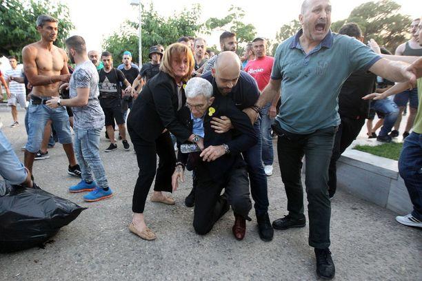 Avustajat auttoivat pormestarin ylös maasta ja pois paikalta.