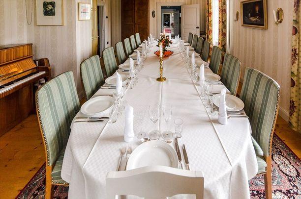 Ruokailuhuoneessa on valtava ruokapöytä, kuten kartanossa kuuluukin.