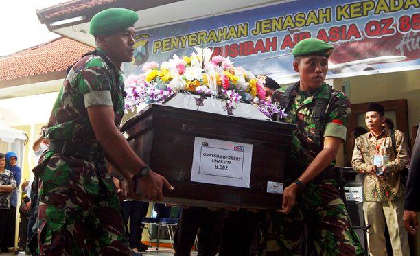 Indonesialaiset sotilaat kuljettavat AirAsian lentoturmassa kuolleen ruumista.