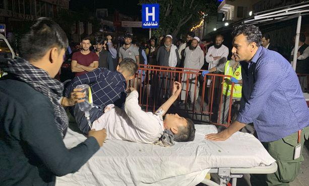 Loukkaantunutta lasta vietiin yöllä sairaalaan Kabulissa tuhoisan pommi-iskun jälkeen.