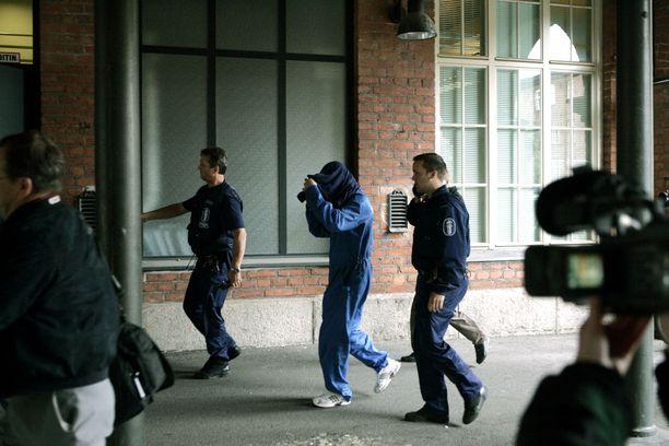 Mattia (keskellä vaaleansinisissä haalareissa) kuljetettiin oikeuteen 2004.