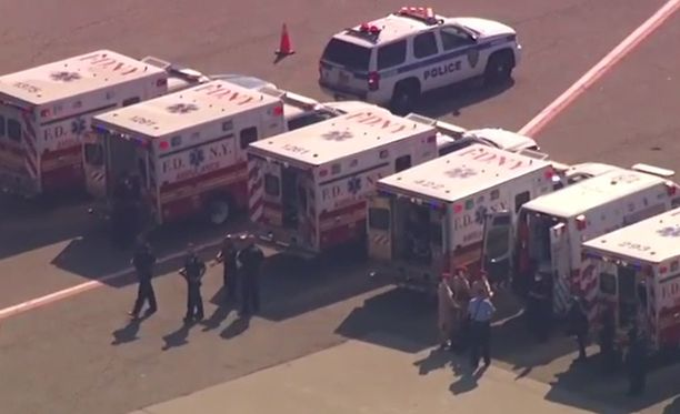 Koneen ympärillä on suuri määrä ambulansseja.