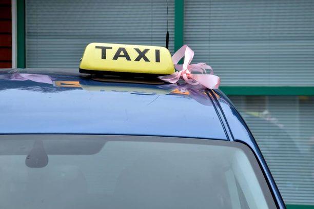 Roosanväriset nauhat sidottiin taksikupuun.
