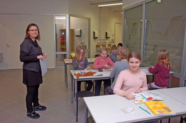 Rehtori Heli Hotti-Paananen opettaa nelosluokkalaisia. Tunteja pidetään myös aulassa sijaitsevien pulpettien ääressä. Etualalla kuvassa on Vilma Lehti.