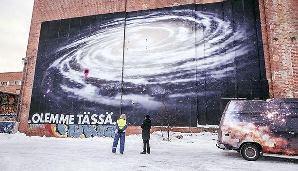 Esko Valtaoja ja Jussi Nygren liisteröivät mittakaavamallin Linnunradasta entisen sellutehtaan seinään.