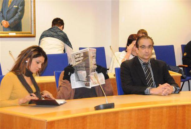 Syytetty piileskeli lehden takana keskiviikon oikeudenkäynnissä. Vasemmalla kuvassa urdun kielen tulkki ja oikealla syytetyn asianajaja Heikki Lampela.