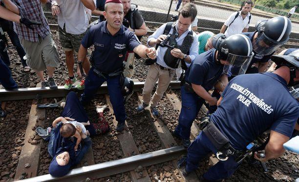 Pakolaisnainen makasi lapsi sylissään rautatiekiskoilla Unkarin Bicskessä. Mies, mahdollisesti hänen aviomiehensä, oli sysännyt hänet siihen hetkeä aiemmin.