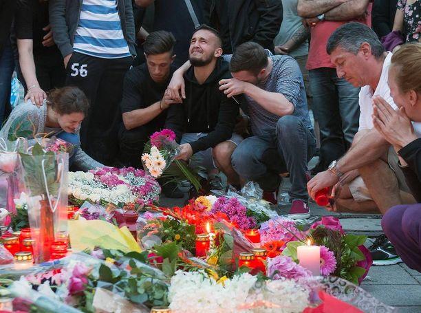 Ihmiset toivat kukkia ja kynttilöitä uhrien muistolle.
