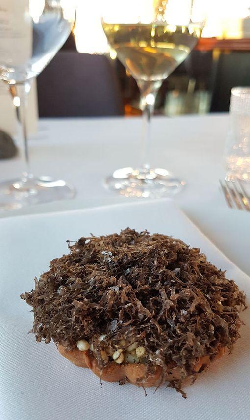 Toni Kostianin tartaletti luomumunan keltuaisella, karamellisoidulla sipulilla, jyvillä ja mustalla tryffelillä.