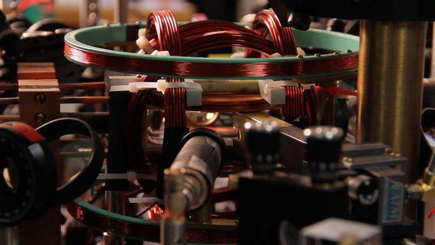 Näkymä laitteiston pääkoekammioon, jossa näkyvät monopolin sisältävän supranesteen muodostamisessa tarvittavat optiset komponentit ja magneettikentän luomiseen käytettävät käämit.