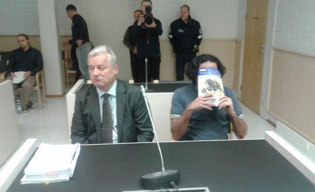 Sekä vanhempi syytetyistä (kuvassa) että nuorempi syytetyistä peitti kasvonsa oikeudessa tiistaina. Kuvassa myös vanhemman syytetyn asianajaja Mikael Knuuti.