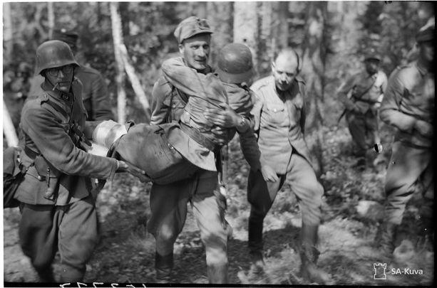 Haavoittunutta kannetaan autoon Vammeljärvellä 14. kesäkuuta.