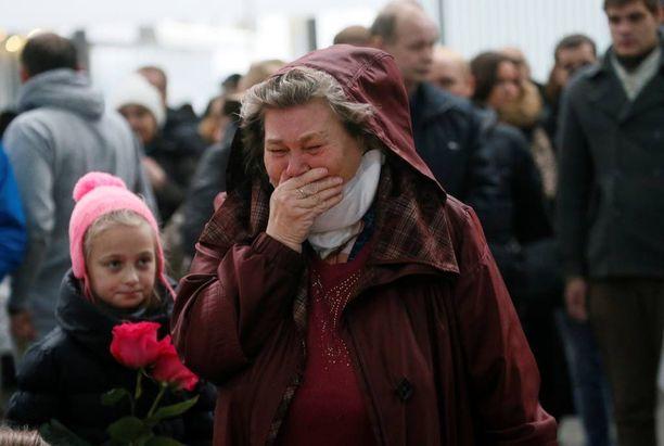 Ihmiset itkivät viedessään kukkia ja pehmoleluja lentoturmassa kuolleiden muistolle Pietarin lentokentän ulkopuolella.