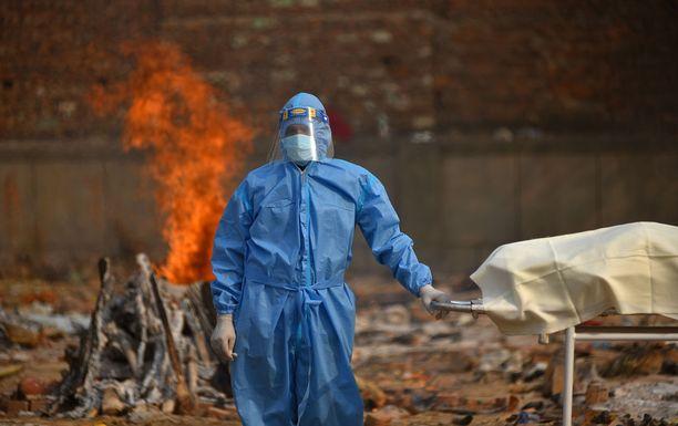 Intian koronavirustilanne on maailman pahin. Kuvassa suojavarusteisiin pukeutunut työntekijä sekä koronavirukseen liittyvään tautiin kuolleen potilaan ruumis Intian New Delhissä.