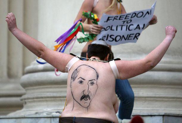 Aktivistit olivat pukeutuneet presidentti Lukashenkoksi, ja yhdellä heistä oli myös tämän kuva piirrettynä selkäänsä.