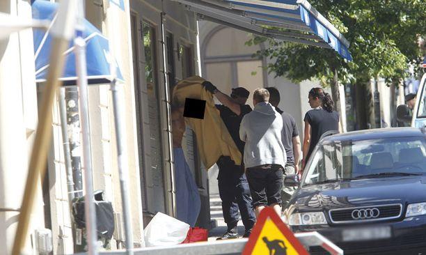 Poliisi talutti pankkiryöstäjän pois ryöstöpaikalta.