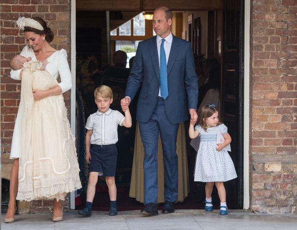 Prinssi William taluttaa prinssi Georgea ja prinsessa Charlottea. Prinssi Louis äitinsä sylissä kastejuhlallisuuksien jälkeen.
