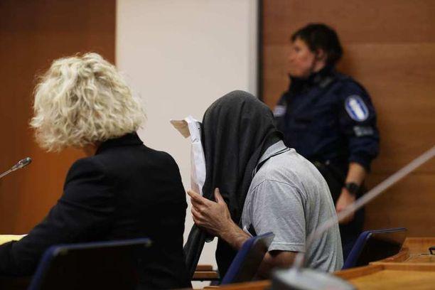 Vastaaja saapui oikeuteen poliisisaattueessa. Mies peitti kasvonsa pään yli vedetyllä paidalla ja kirjekuorella.