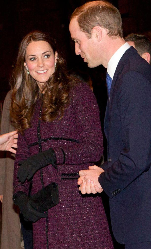 Kate suojeli vatsakumpuaan kädellään ja laukullaan.
