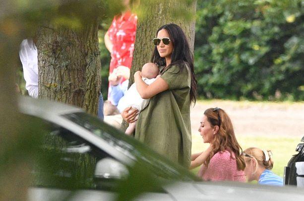Herttuatar Meghan sylissään pieni Archie, taustalla lastensa kanssa leikkivä herttuatar Catherine.