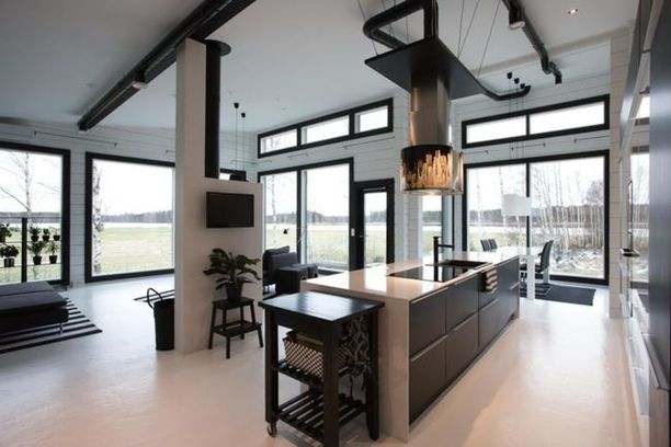 Mustan hirsitalon värimaailma jatkuu sisätiloissa. Asunnossa on industrial-tyylisiä ratkaisuja.