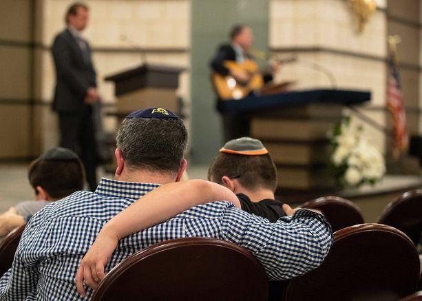 Isä ja poika lohduttivat toisiaan lokakuussa floridalaisessa synagogassa Pennsylvanian tuhoisan synagogaiskun jälkeen.