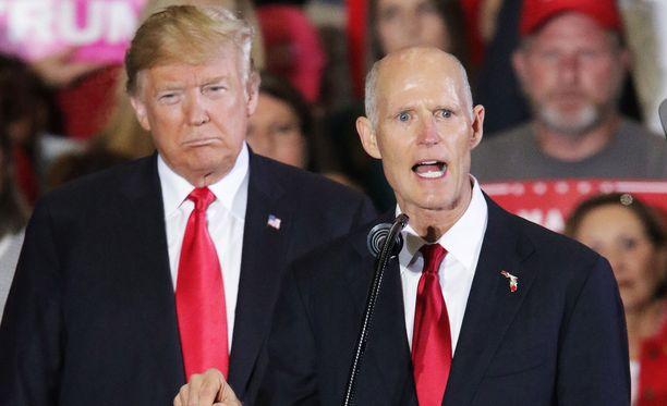 Floridan senaattorikisan tiukasti voittanut Rick Scott vaalitilaisuudessa presidentti Donald Trumpin kanssa 3.11.2018.