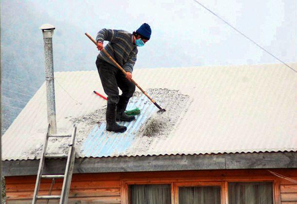 Tuhkatöissä Chileläismies putsasi maanantaina kattoaan Futaleufun kaupungissa Chaiten-tulivuoren syljettyä tuhkaa ilmaan jo neljäntenä peräkkäisenä päivänä.