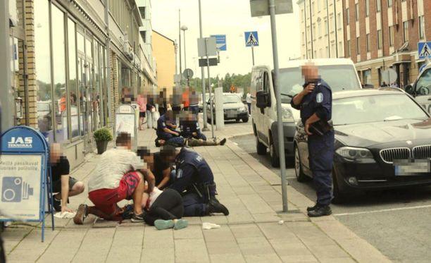 Kuvassa puukotustilanne on juuri päättynyt. Etualalla ihmiset auttavat yhtä uhreista, takana poliisi pitelee maassa haavoittunutta puukottajaa.