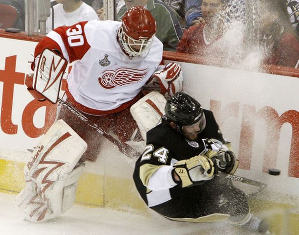 Pittsburgh Penguinsin Matt Cooke ja Detroit Red Wingsin maalivahti Chris Osgood kiekon perässä.