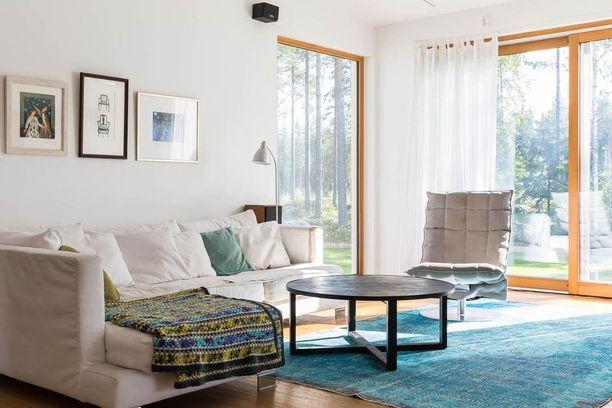 Vaalea sohva herää eloon, kun sitä somistaa värikkäillä tyynyillä ja torkkupeitolla.