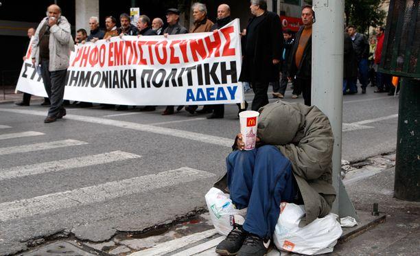 Kerjäläinen istui kadun reunassa Ateenassa. Taustalla mielenoositus.