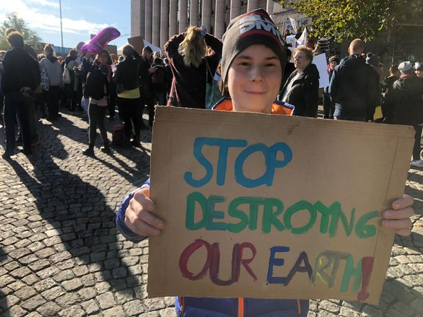 """""""Stop destroying our earth!"""" luki kahdeksasluokkalaisen Topias Mielosen kyltissä."""