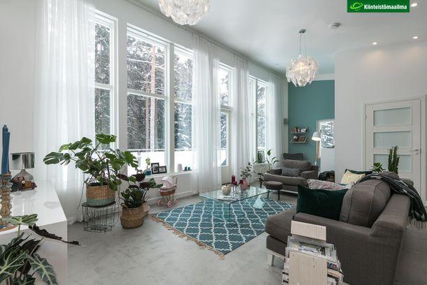 Näyttävä huonekorkeus ja isot ikkunat ovat tämänkin modernin kodin peruselementtejä. Mukaan on saatu myös hieman väriä tehosteseinän ja maton avulla.