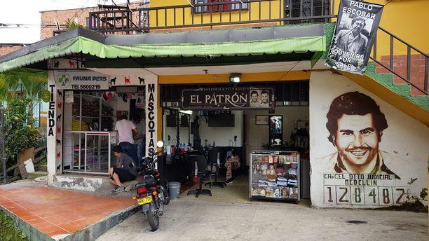 """Narcos toi Escobarin viiksineen ja dollareineen takaisin katukuvaan. Ihmiset myyvät aitoja ja vähemmän aitoja Pablo-kirjoja, """"Plata o plomo"""" -t-paitoja ja tarroja Escobarin ikonisesta pidätyskuvasta."""