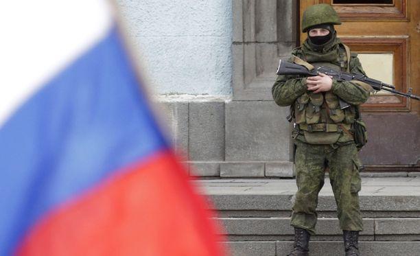Aseistautunut mies vahti hallintorakennusta Krimissä.