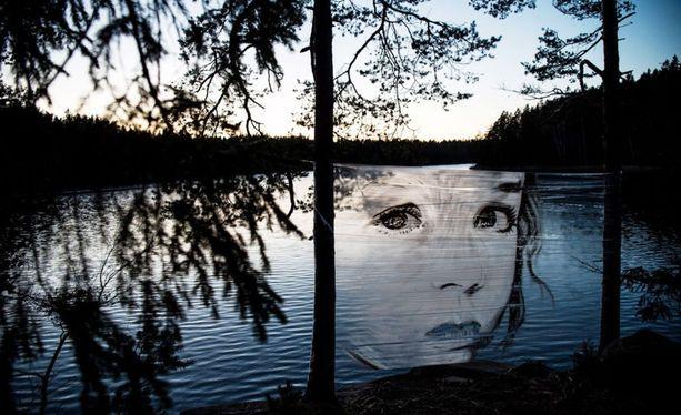 Oikeasta suunnasta katsottuna taideteos luo lapsen kasvot veden päälle.